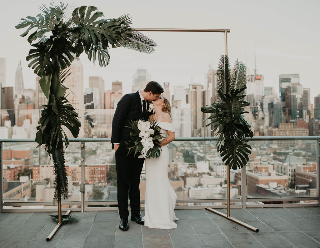 Paige and Justin Wedding - Bride and Groom Kissing Tropical Foliage Arch - The Press Lounge - Cheyanna De Nicola Photography