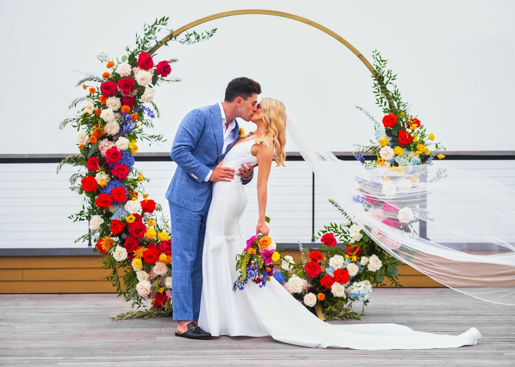 Dayna and Matthew Wedding - Bride and Groom Kissing Bouquet Moongate Flower Arch - Gurney's Montauk - Andreas and Nico
